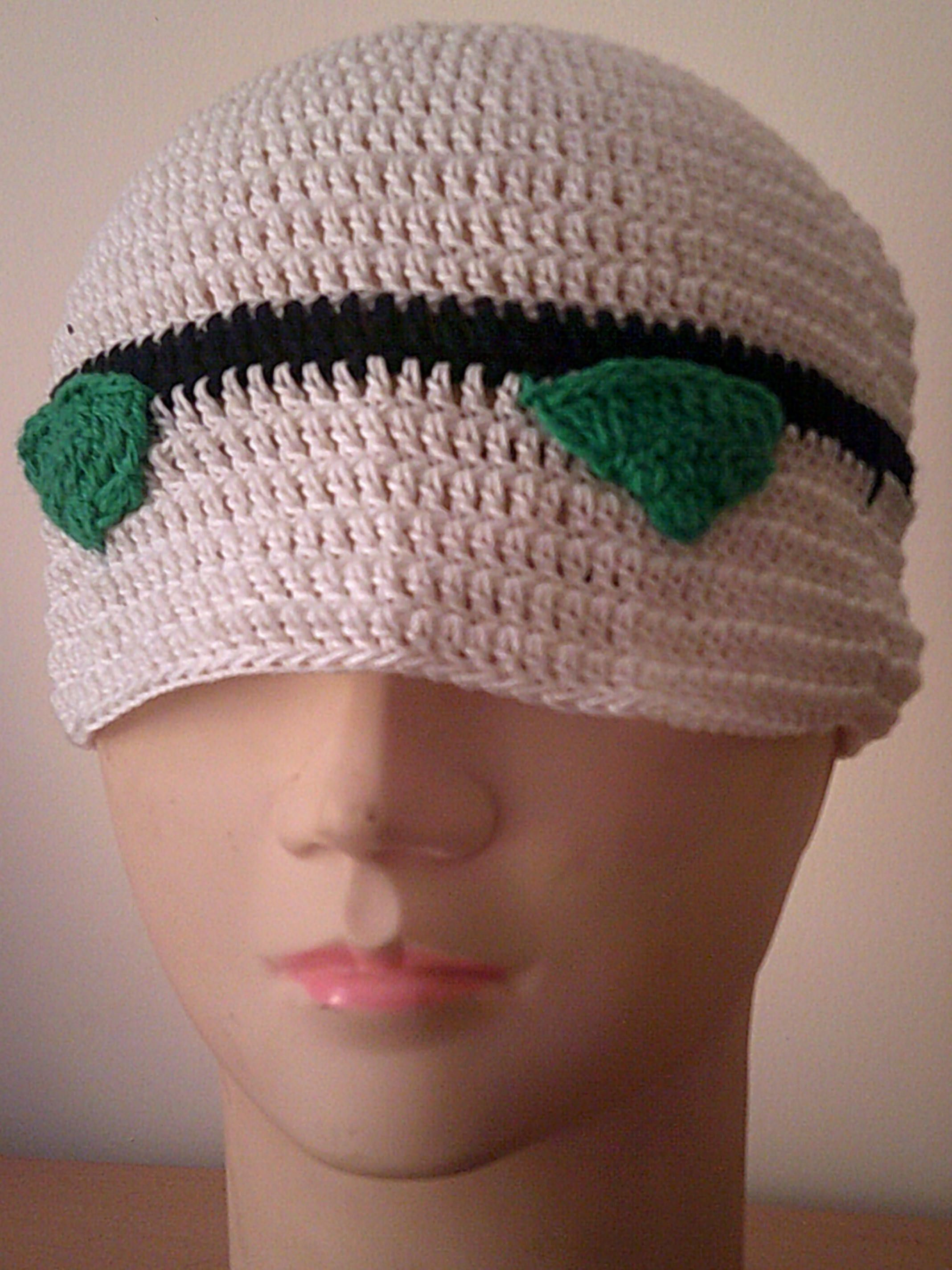 White hat, decorated with black stip and two green eyes. Inspired.