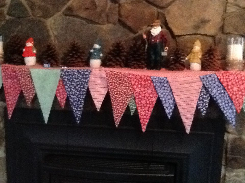 Reversible mantle banner. Triangles are cut 8.5 in x 10.5 in and 8.5 in x 14.5 in. I used snowflakes/stripes for one side and woodland/holly prints for the other. Sewed with 1/4 inch seams, turned and pressed, leaving top open. Cut 2 rectangles the size of my mantle and layered the triangles between them. Sewed them all together along one long edge and both sides, flipped and top stitched the back long edge. Done.(This is mine!)