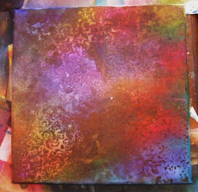 """Neelz Expressionz: """"I started off with a 12 x 12 canvas and sprayed it liberally with Dylusions inks (most of the new colours) I added details using a Prima Flourish mask and water and dried it off with the heat gun. I added some Perfect Pearl sprays too though you can't see the sparkle here."""""""