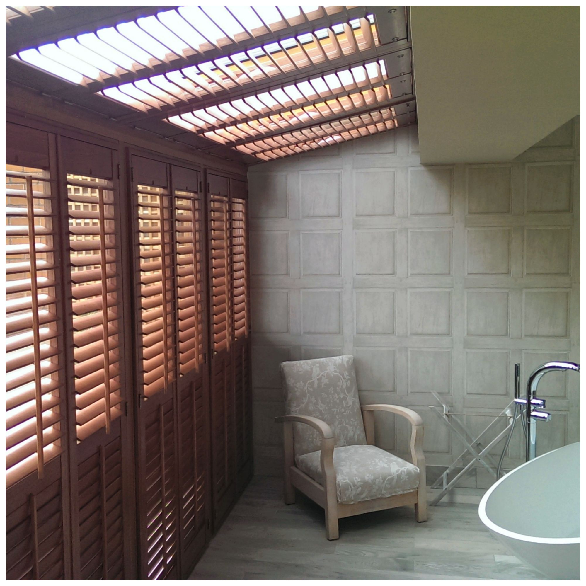 We installed premium hardwood plantation shutters, incorporating a balcony door cutout. The custom colour for the whole design was Sapele. A mix of 63mm louvres (designed for the window plantation shutters) and 89mm louvres (for the roof windows) were incorporated into the design. The finished project features antique brass hardware astragal doors, with spring loaded catches at the top and hinges at the bottom. An electronic remote control manages the tilt system of the angled roof windows.