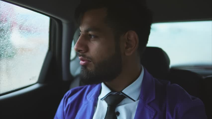 Ad: Young muslim businessman riding in the car on passenger's seat ...