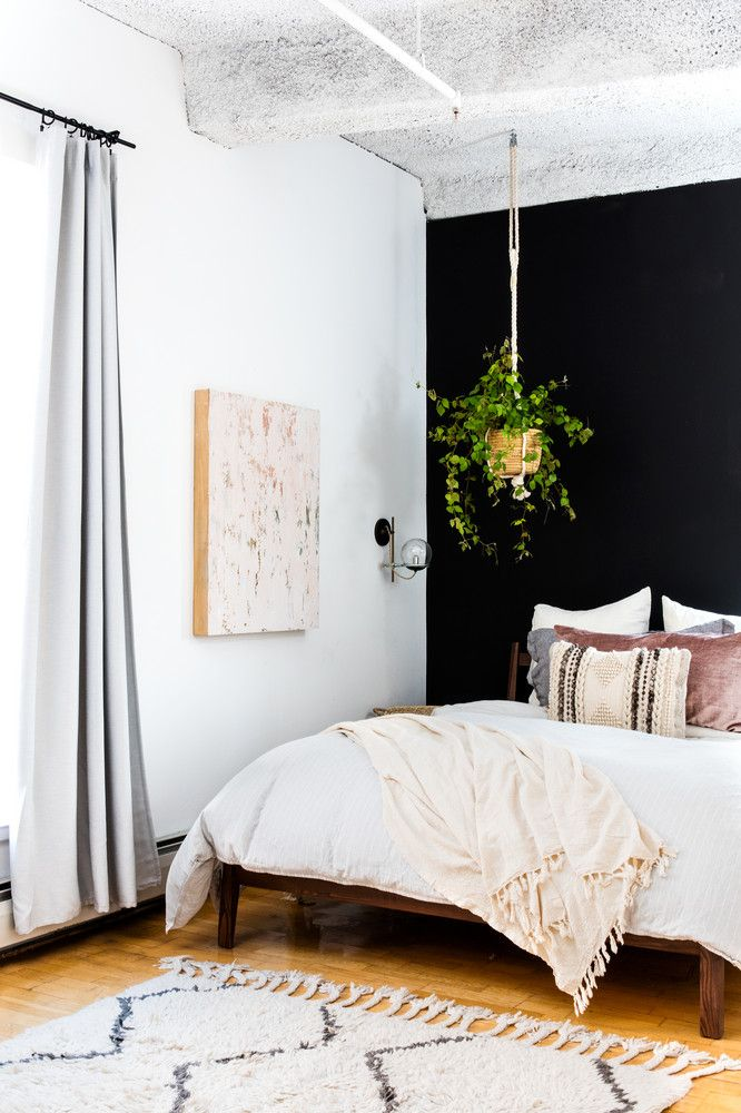 a white boho chic bedroom with black accent wall