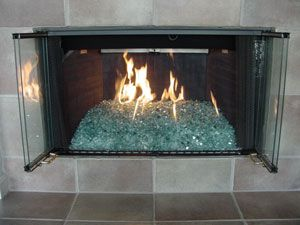 fire on glass custom fireplace - example of the layering process for the glass and using sand and lava rock filler under the glass.