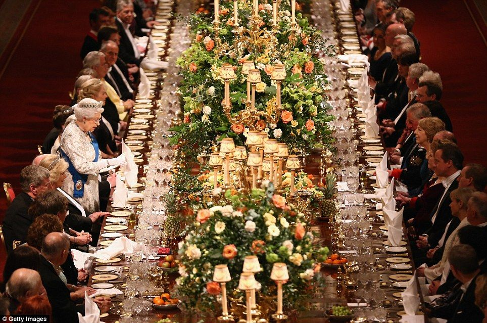The long polished table - surrounded by 160 guests - was decorated with candelabras and fl...