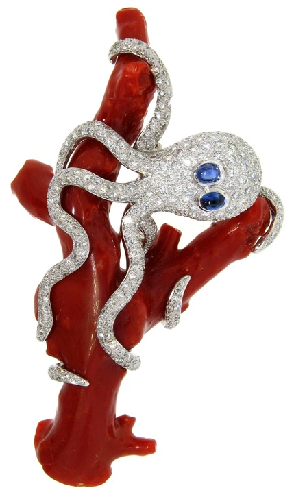 Sapphire, coral and diamond brooch in the shape of an octopus entwined on a branch of red coral with 2 cabochon cut blue sapphires weighing 0.30 carats and numerous pave set diamonds weighing 6.00 carats.