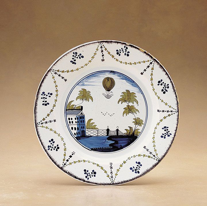 """Title: Dish Date: ca. 1785 Place: Lambeth, London Format: Delftware / H.: 1 3/4"""" (4.4 cm); Diam.: 13 1/2"""" (34.3 cm) Description: Full view: top Decoration: Painted. Commemoration of Vincenzo Lunardi's balloon ascent. Border composed of concentric circles, sprigs, swags, and pseudoshell edge."""