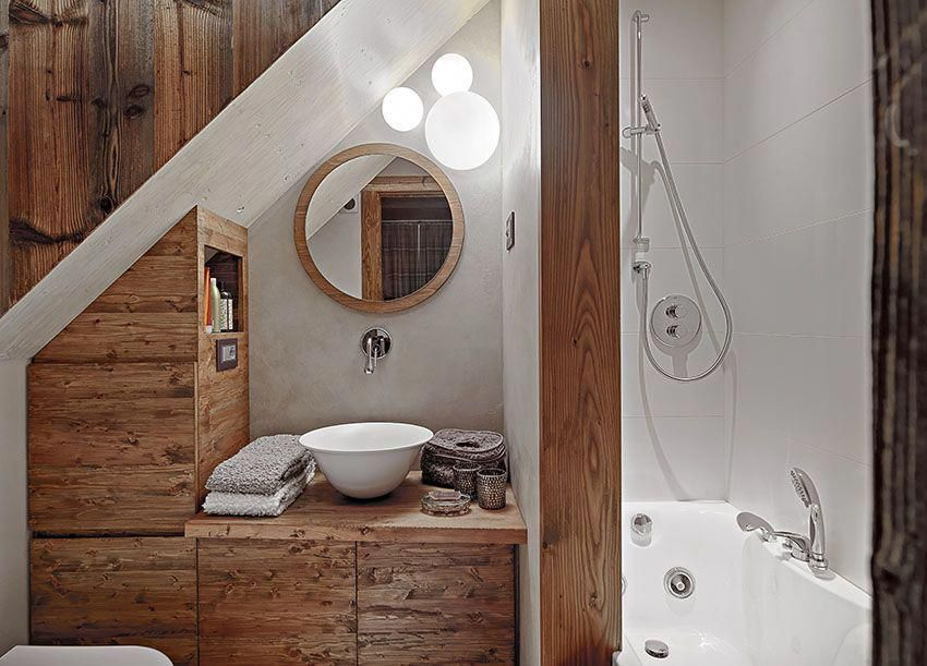 Small Attic Bathroom With Slanted Ceiling And Pedestal Sink