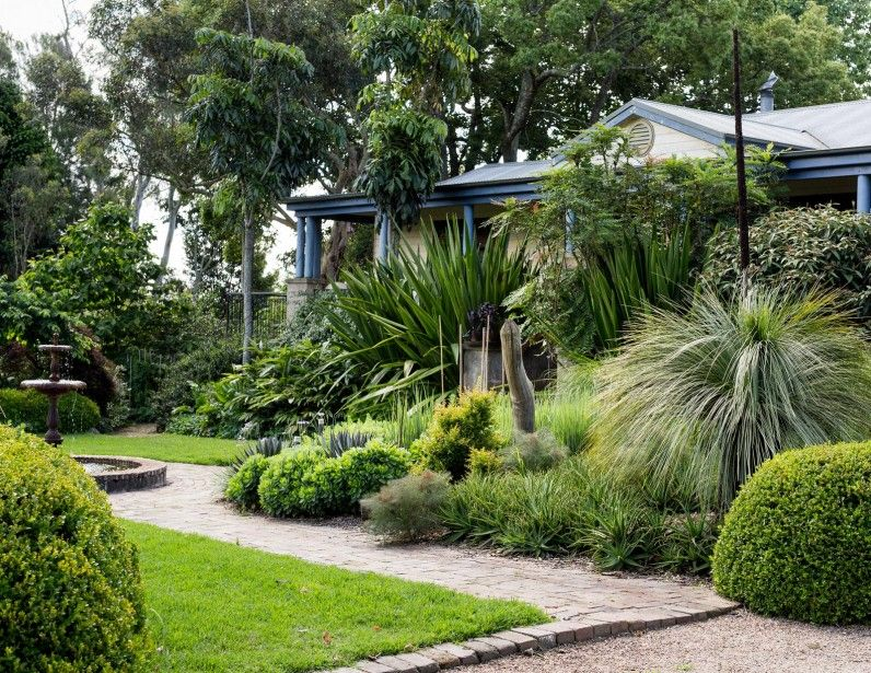 the house entry is framed by lush mixed plantings of gymea