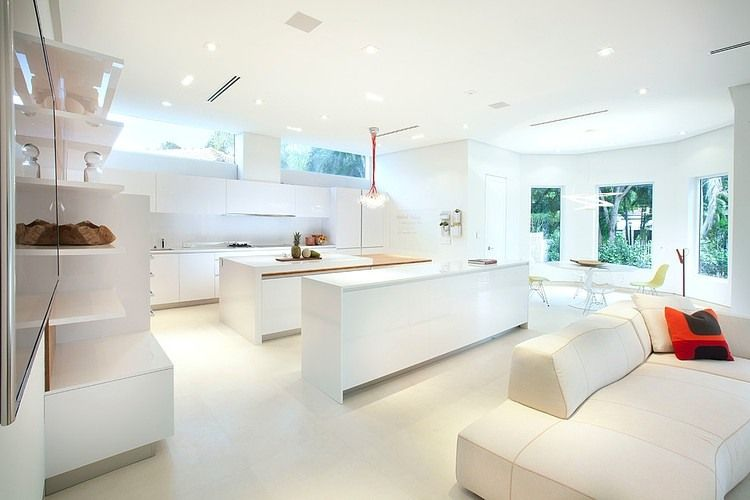 white, minimalist kitchen with windows and island.  the kitchen is in the back corner of the house, so it will have good views of the backyard and trees.  we'd like for the gas range to be in the island since we love korean bbq dinners and would like to use the island to grill as we sit and eat.