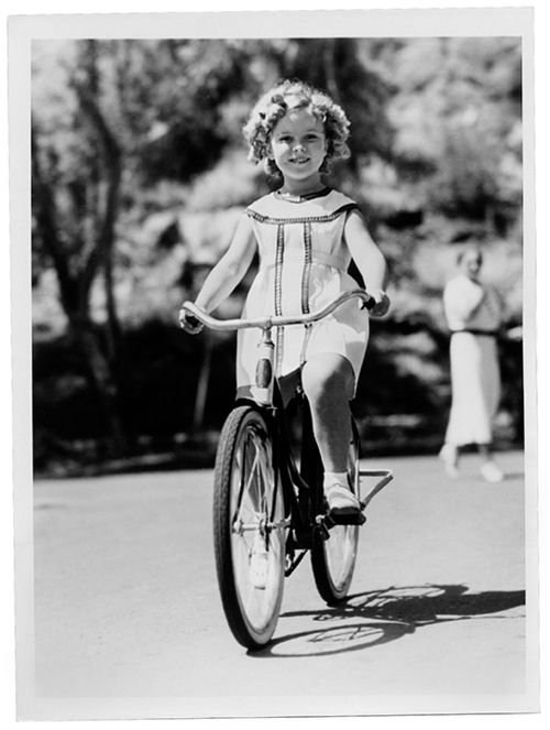 Acme Newspapers photo caption: A Veteran Novice: Shirley Temple won't ride her velocipede any more since she's learned to handle a bicycle. Here she is seen shortly after her first lesson riding down a street of Palm Springs Calif. 4/18/36