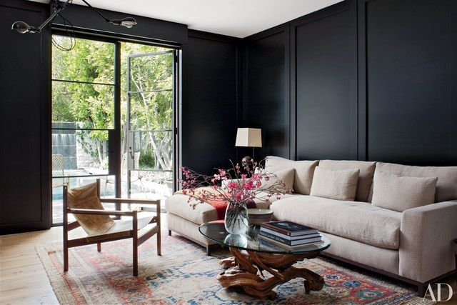 In a Beverly Hills study designed by architects Silvia Kuhle and Jeffrey Allsbrook, a midcentury armchair from Blackman Cruz is grouped with a vintage glass-top driftwood table and a custom-made sectional by Molly Isaksen Interiors upholstered in a Wyeth linen.