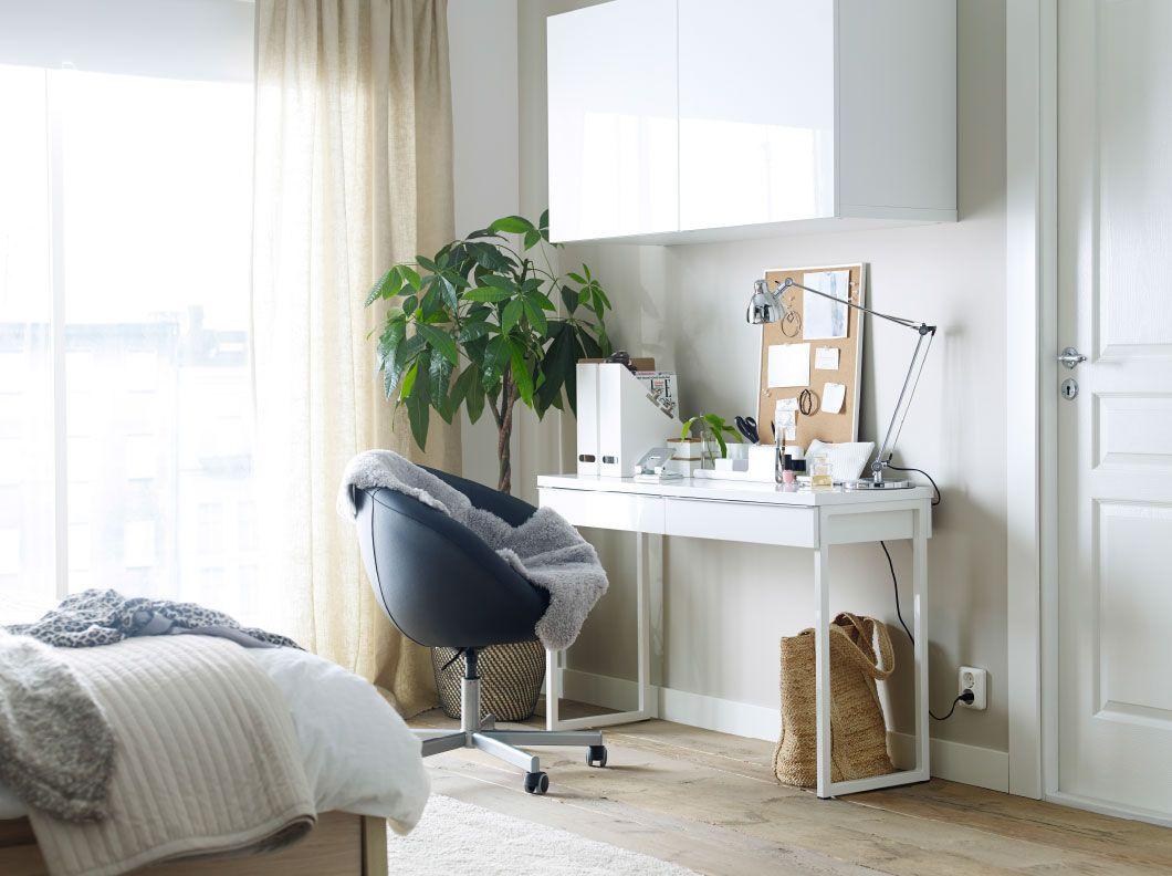 Et hvitt skrivebord med en svart arbeidsstol på hjul og et veggskap på soverommet.