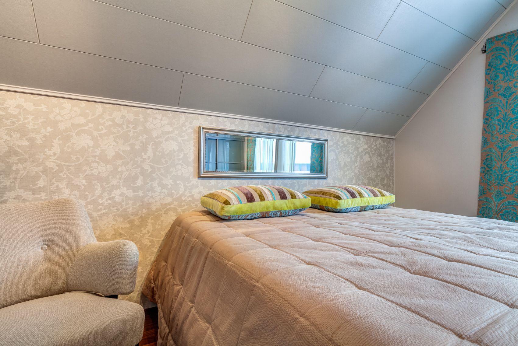 Makuuhuone. Tässä tilassa on ollut kaksi pientä makuuhuonetta, mitkä remontin yhteydessä yhdistettiin yhdeksi suureksi tilaksi. Yläkerran katto madaltuu molemmin puolein. Toiselle seinälle on sijoitettu pitkä rivistö vaatekaappia peililiukuovilla.