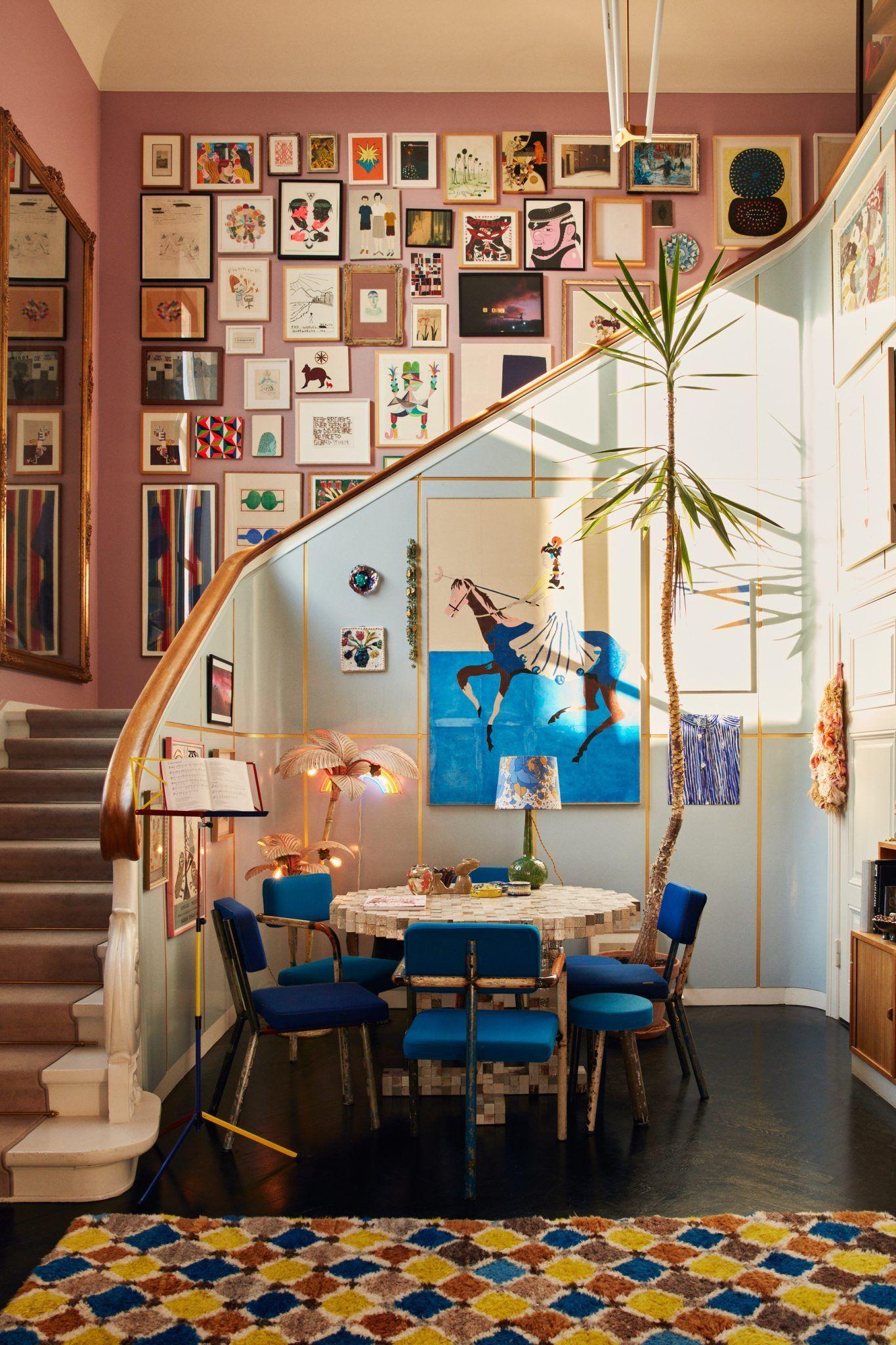 Photo of Blauer und rosa Wohnraum mit großer Galeriewand im Treppenhaus in einem …