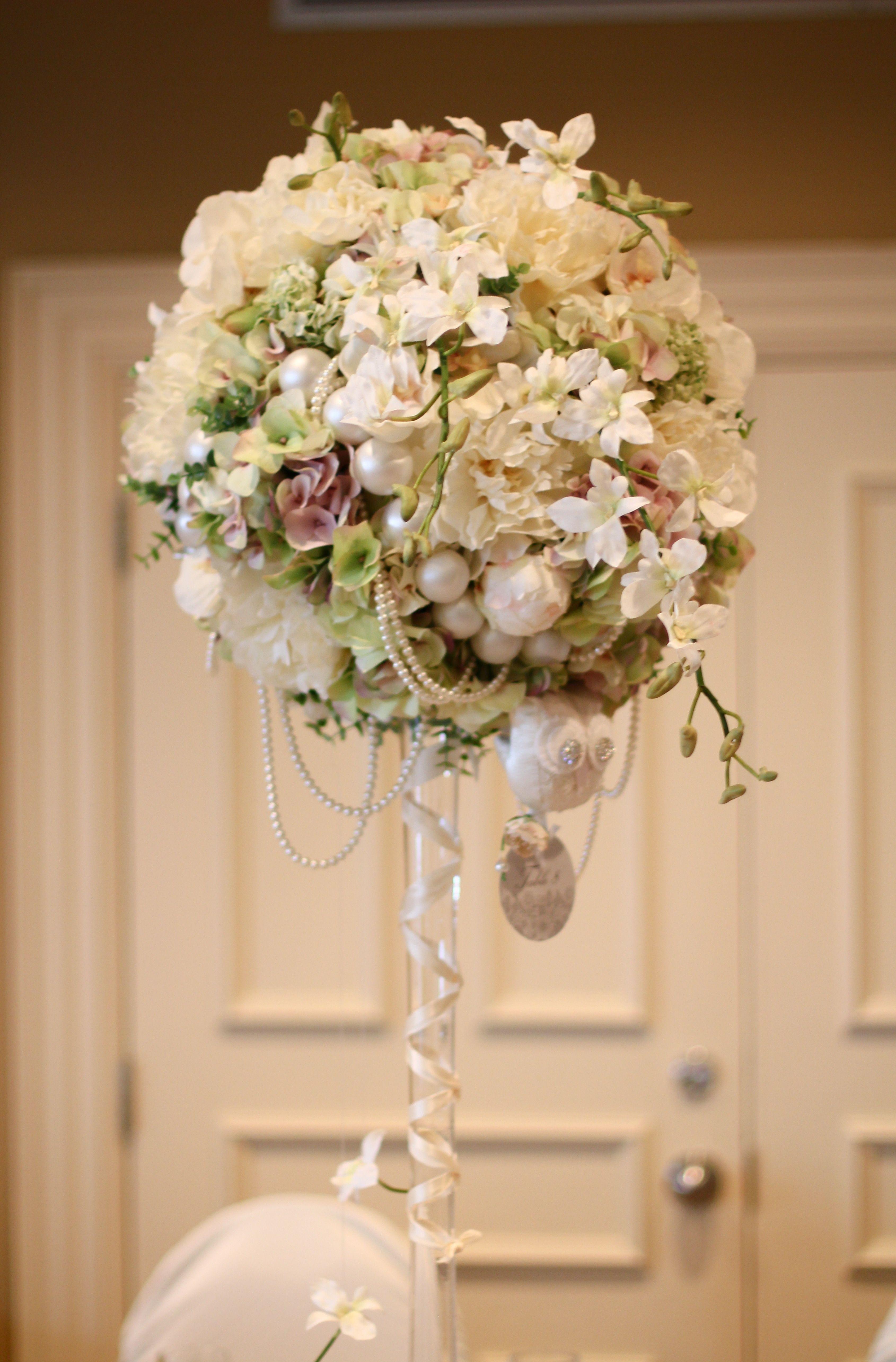 A creative centerpiece using artificial flowers and pearls.  Une centre de table créatif fait en fleurs artificielles avec des perles.