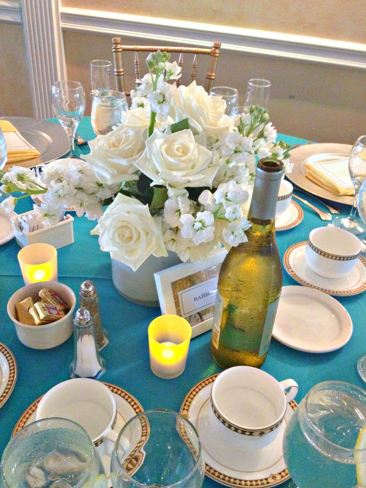 Gorgeous White Centerpieces Pop On The Sleek Turquoise Linens