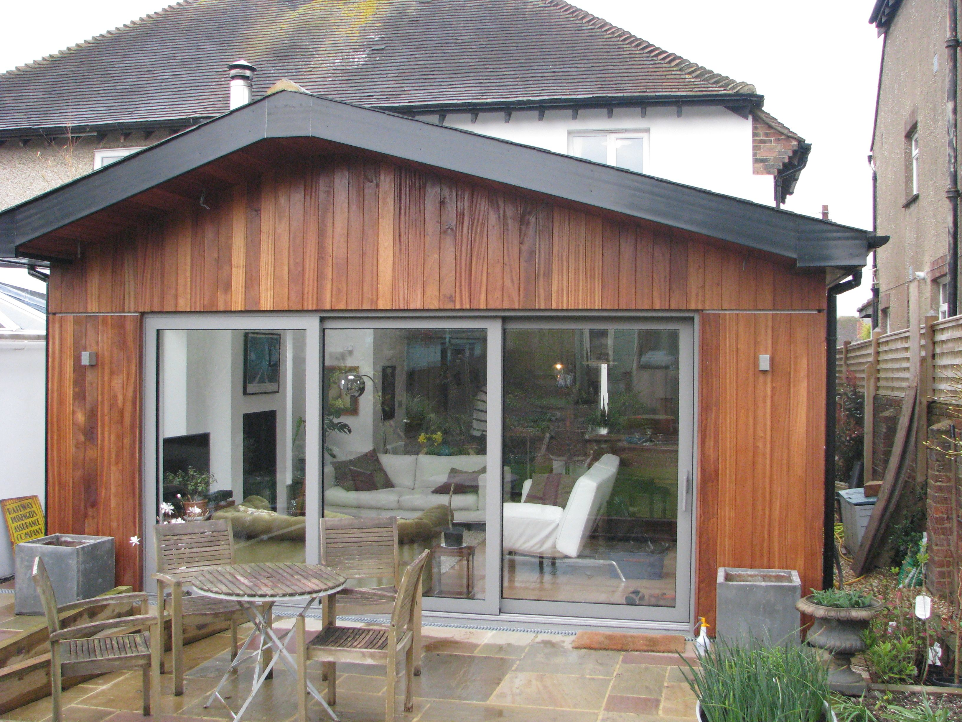 Rear extension | pitched roof | vertical timber cladding | grey aluminium sliding doors | residential |