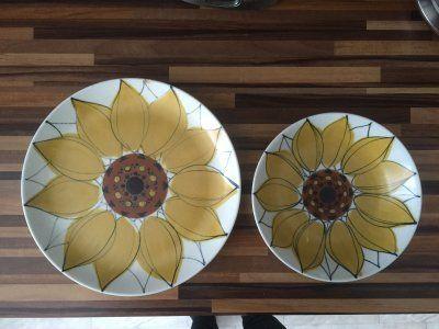 Lautasten koristeen on suunnitellut Hilkka-Liisa Ahola. Koristeen nimi on Aurinkoruusu. Lautaset ovat Arabian valmistamaa AR-mallia, jonka suunnittelija on Kaarina Aho. Tuotannossa kokonainen astiasto tällä koristeella on ollut vuosina 1960-1975. Lautasten pohjamerkintä on tyypillinen Arabian koristeille, jotka on tehty käsin maalaamalla.