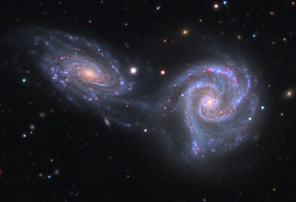 """As duas galáxias que você vê na foto estão """"algemadas"""". Isso é, elas trombaram e estão ligadas por suas forças de atração. Daqui a muito tempo, elas podem se soltar ou se fundir e formar uma grande galáxia! Namoro versão cósmica."""