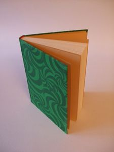 """The Bradel binding, also known as a Built-In-Groove binding, is a traditional German style case binding usually covered in full paper or cloth. In this style, the cover boards are joined with a """"lapping"""" component before covering, & the groove is formed as an integral structural component. These structural differences result in a sleek, streamlined, & highly functional book."""