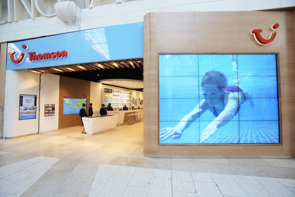 A large video wall outside of Thomson's new store greets customers with color travel pictures.