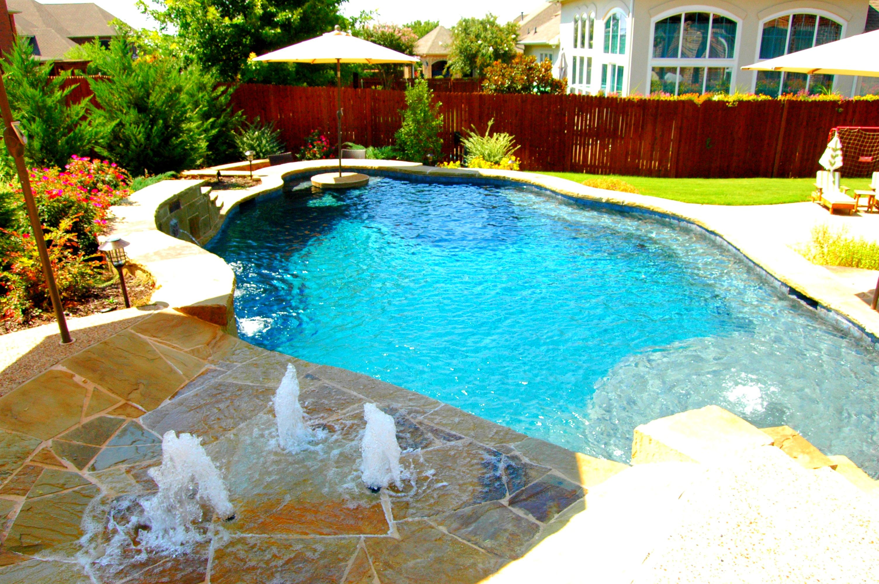 Another stunning example of a freeform pool with tequila table and splash pad by dallas fort for Fort worth swimming pool builders