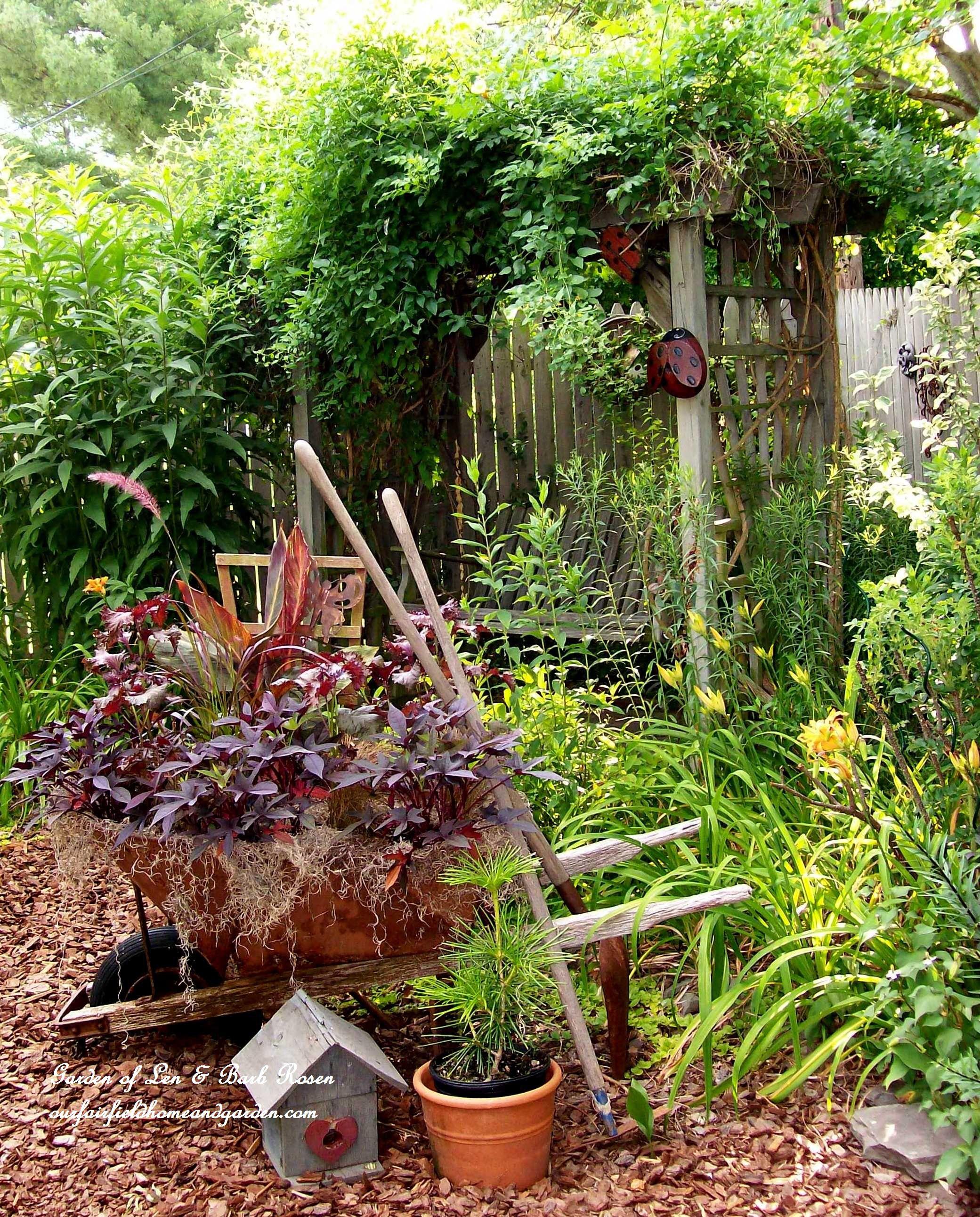 Wheelbarrow planting and arbor swing garden of len u barb rosen