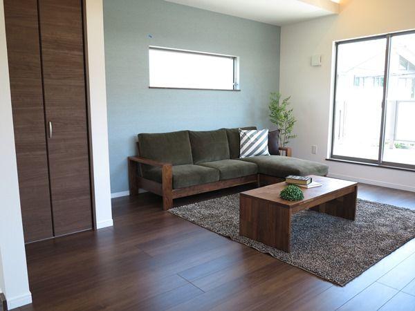 クリエモカ色のフローリングにウォールナット無垢材の家具で