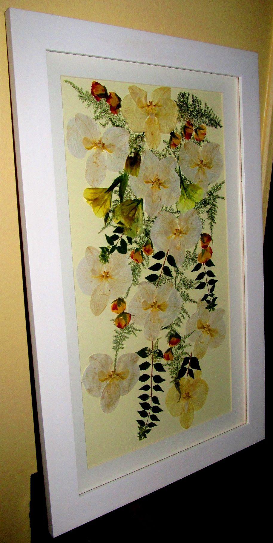 Ramo de novia prensado y enmarcado con orquídeas blancas.