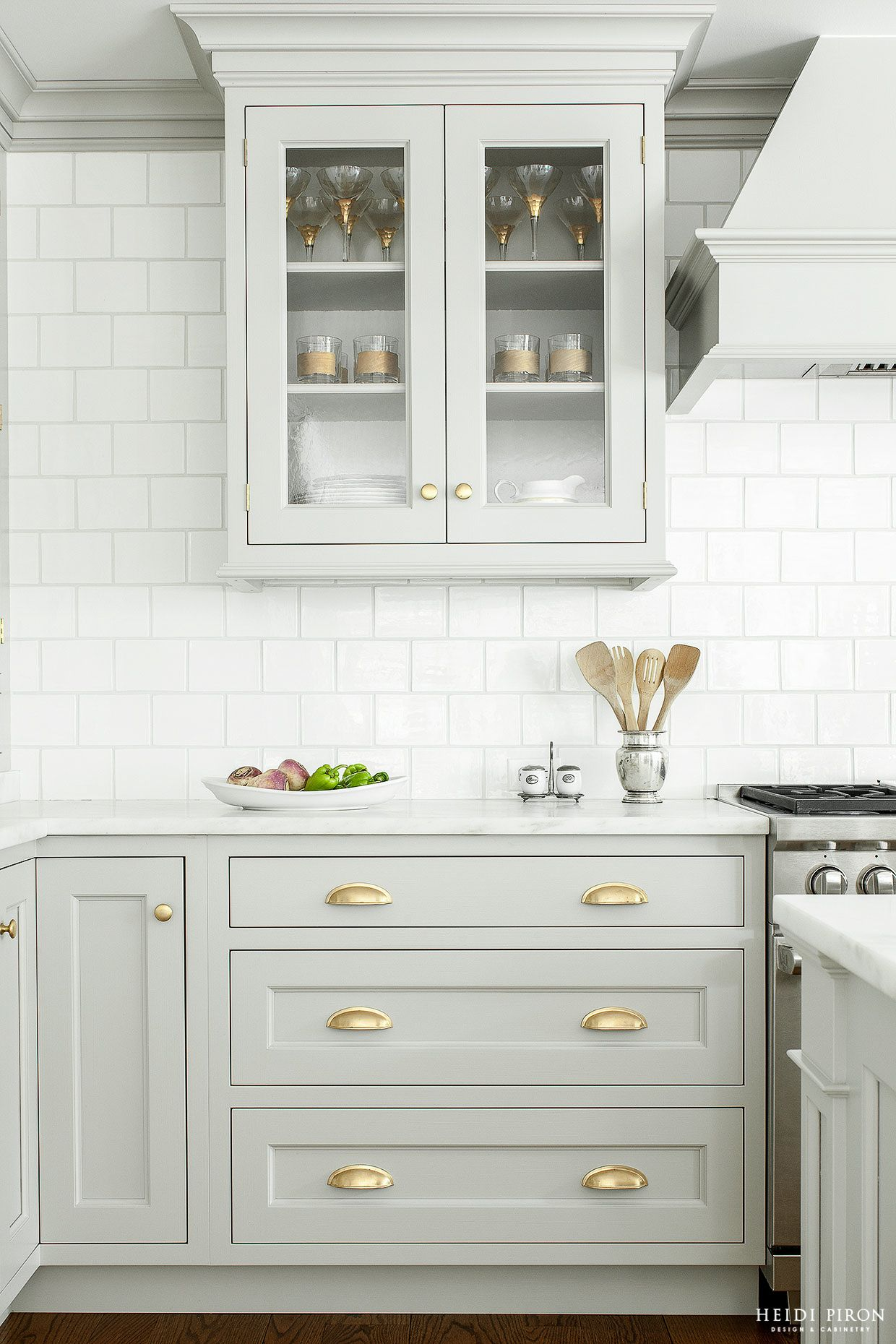 Gray cabinets with glass doors and gold hardware, white subway tile ...