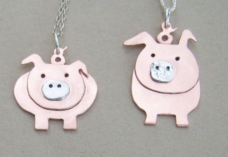 A pair of copper pig pendants.  With sterling silver snouts and chains.