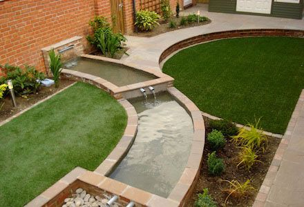 cascading pool water feature separating two large circular lawns