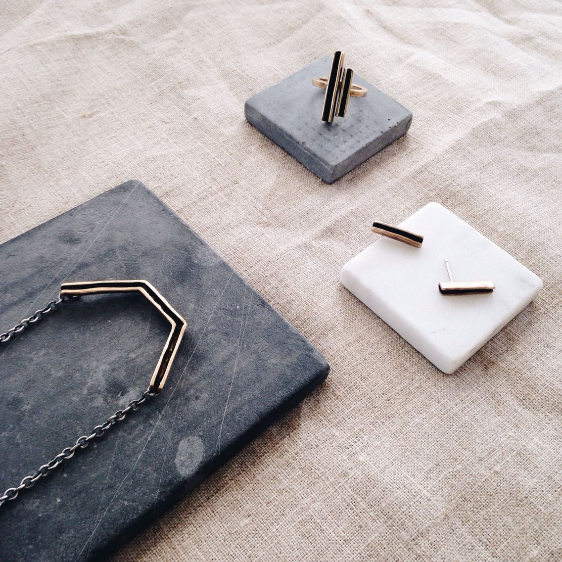 The Parallel Collection in Bronze and Sterling silver resting on grey tiles.  www.blessthetheory.com