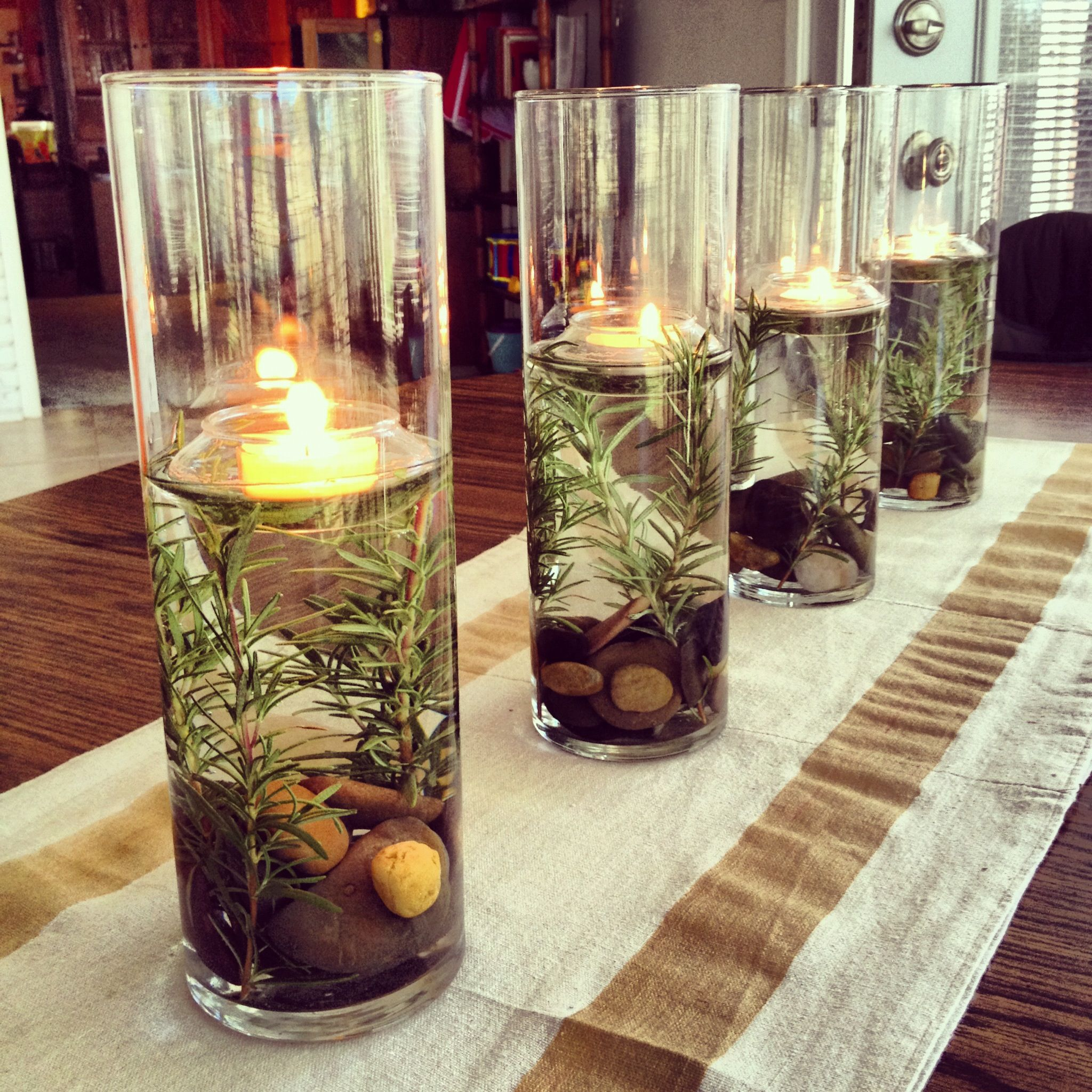 festive centerpiece river rocks rosemary floating tealights