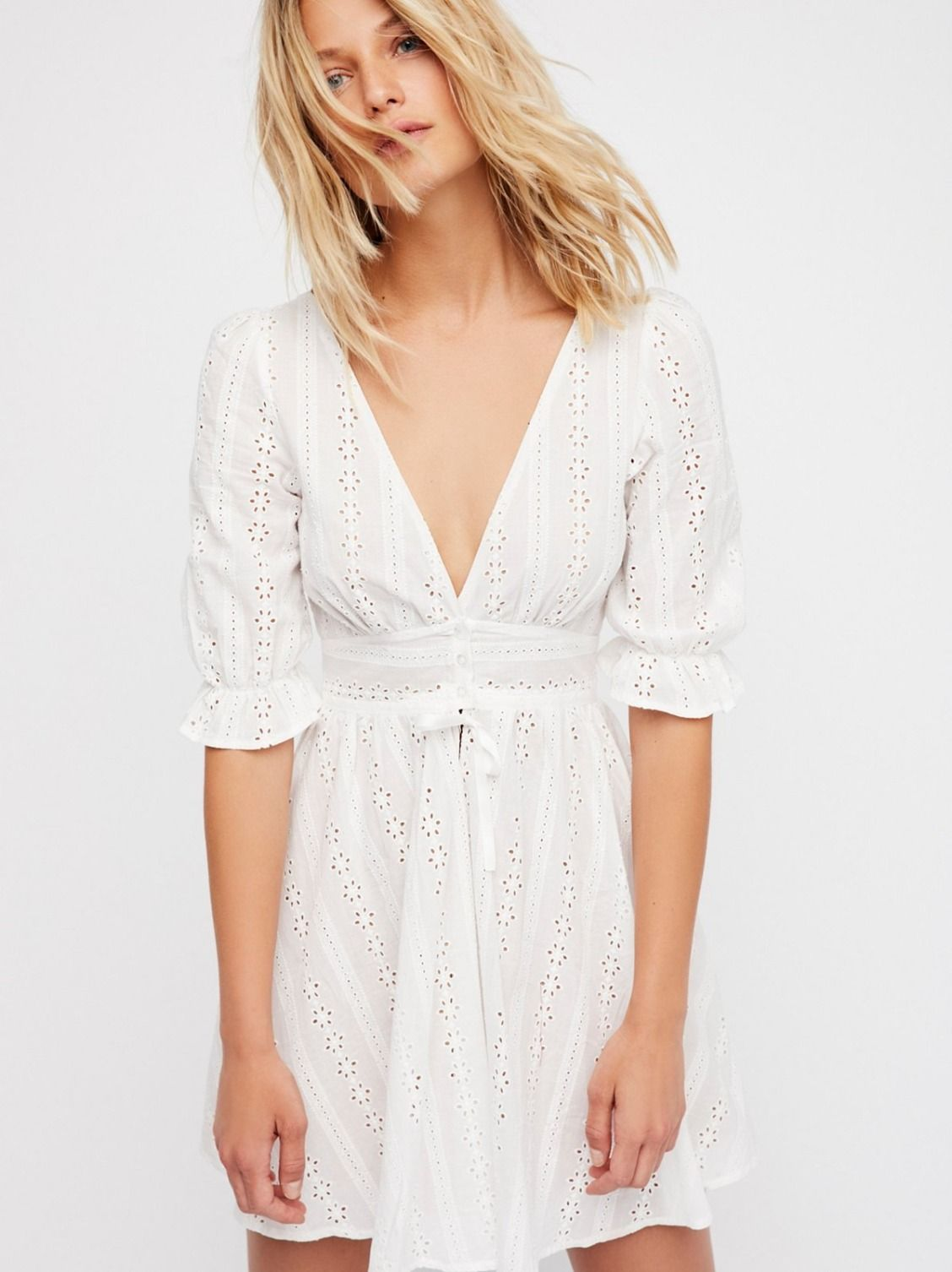 Cotton Eyelet Dress | This light and easy cotton eyelet sundress is the sweetest mini dress featuring a puff sleeves with ruffle trim.  * Plunging neckline * Center button closures * Decorative tie detail * Full skirt * Fitted silhouette * Lined