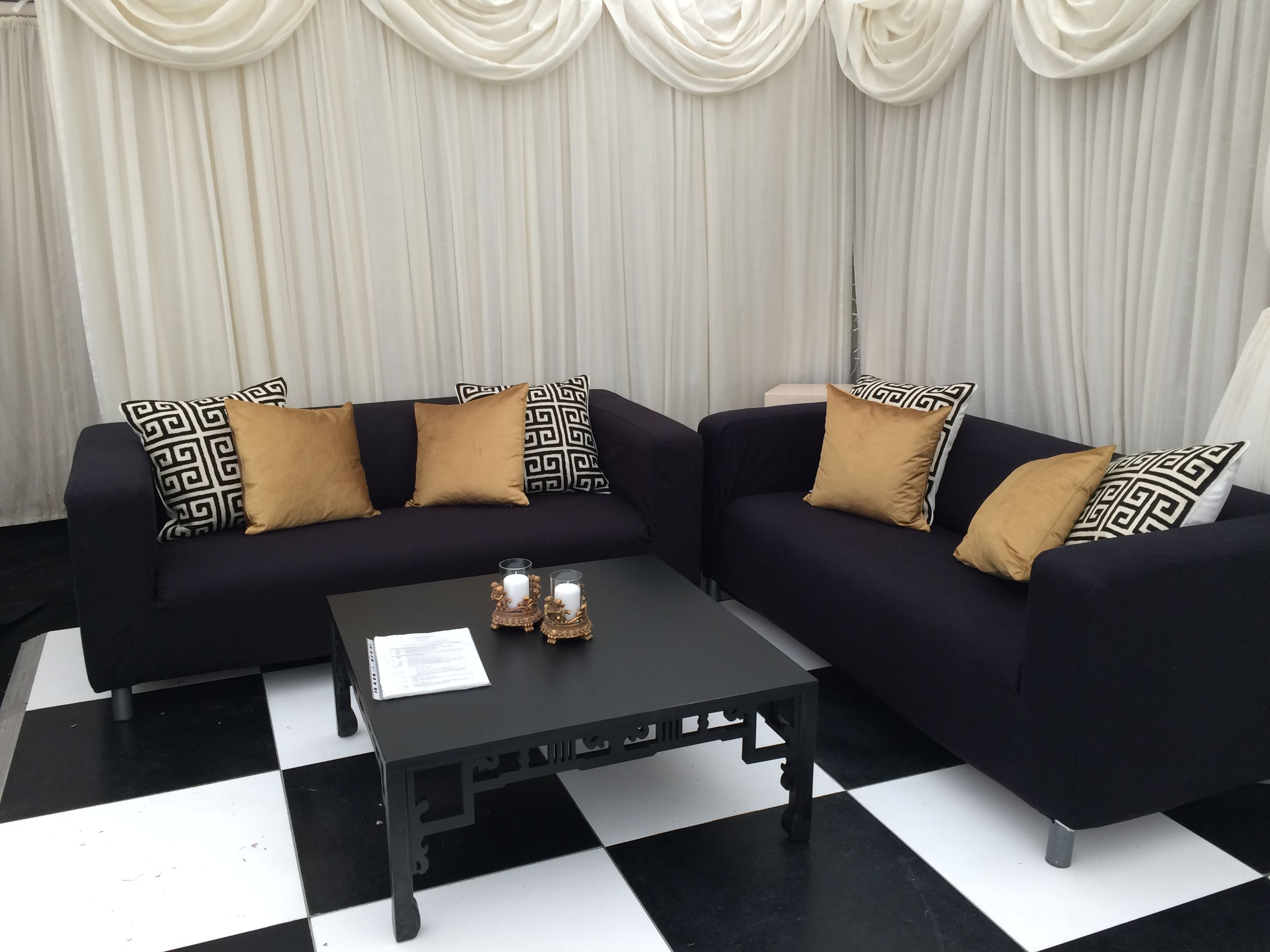 Black sofas with black & gold luxury cushions in the cake corner