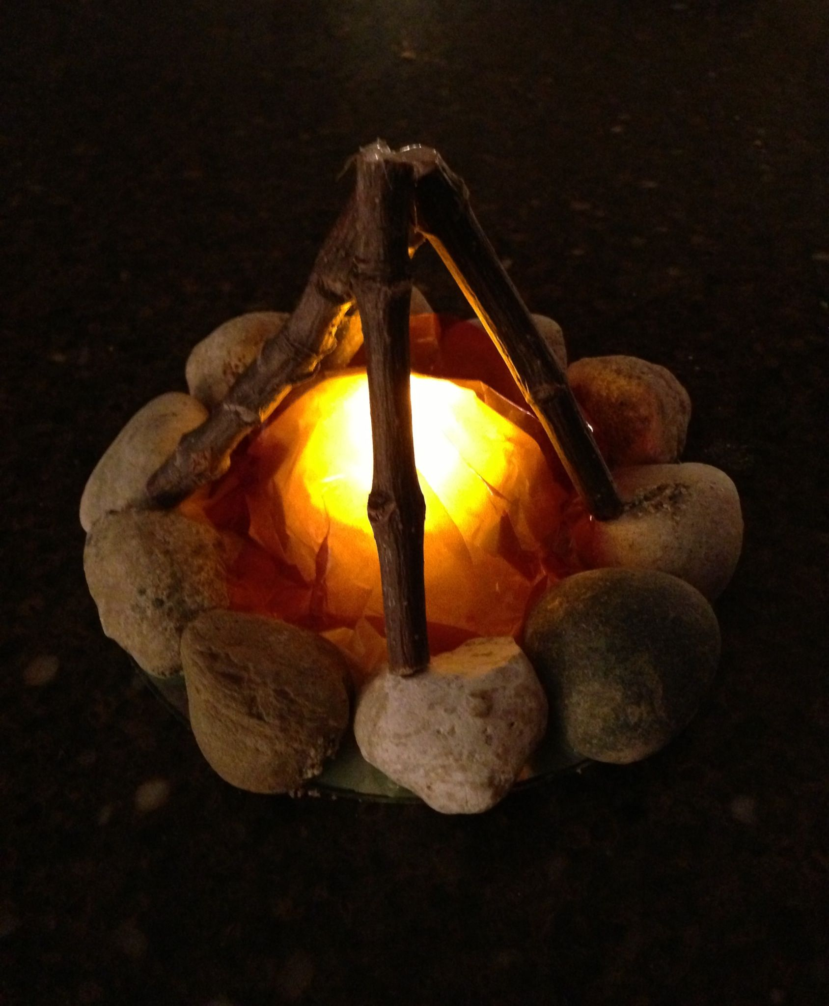 Campfire Nightlight: Glue rocks around perimeter of an old CD with tacky glue. Place battery-operated Tealight in center of CD; do not glue down. Place 4-5 sticks up against rocks in a teepee shape. Use hot glue gun to secure tops together. Trace around CD and cut out one circle each of yellow tissue paper and red cellophane. When glues are dry crinkle papers and place over tealight, place teepee on top to secure.