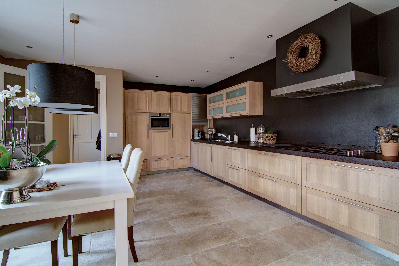 De woonkeuken heeft een complete moderne L-vormige licht eiken ...