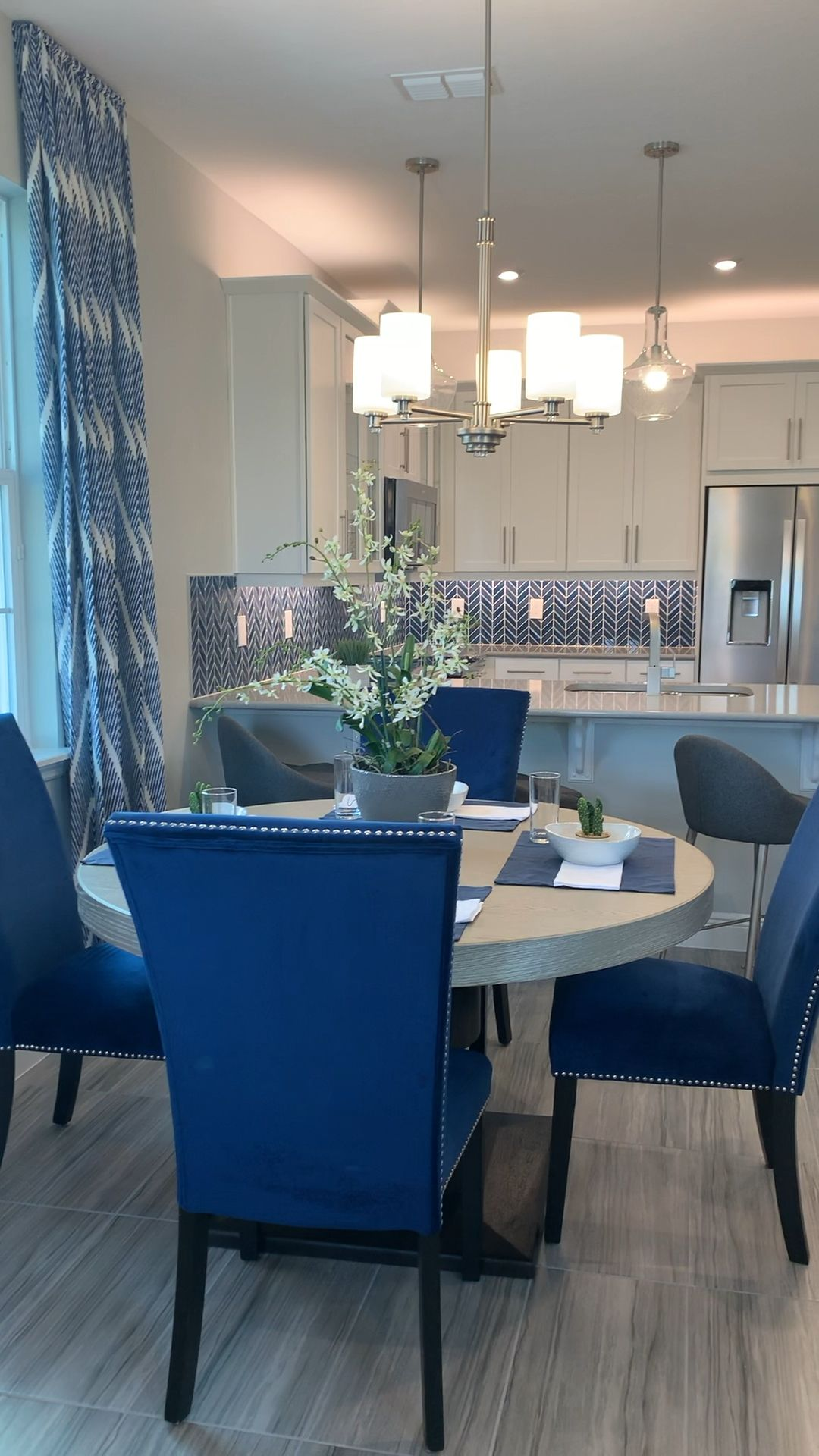 Looking for home Decor Inspiration? 💙 Layers of Blues in patterns and prints throughout this white kitchen open concept design.  Located in Windermere, FL ##FloridaInteriors #TownhomeLiving #bluedecor