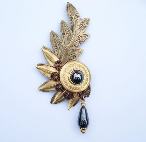 This is a gorgeous, vintage brooch done in an elegant, classic style. It�s 3 �� tall and weighs 14.6 grams.The brooch is done in a variety of layers and style. At the bottom is a large, dark brass curling leaf with an etched design. Over that are brighter relief style leaves and coppered colored...