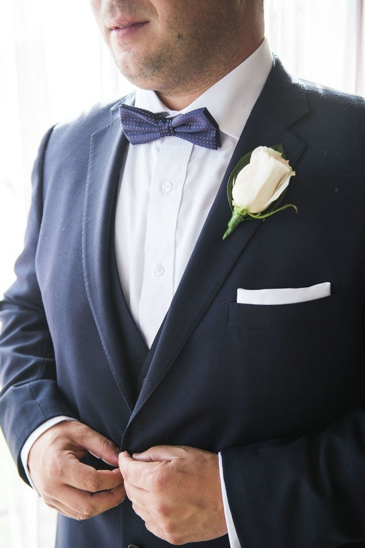 Groom in navy blue suit + Poldka dot navy blue bow tie with blush pink boutonniere #groomstyle #groom