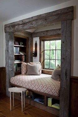 A reading nook needs to be out of the way and cozy, but it also needs to have a small window near it. That way you can stare off into the (well placed) forest of pine trees. Think about sitting by the window on a rainy or snowy day. I would actually prefer the nook to be less open than this one. Or at least have a curtain to close over it.
