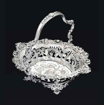 A fine George II silver cake basket, mark of Paul de Lamerie, London, 1739 -  Of large size; shaped-oval, on four cast feet in the form of bearded masks with scrolls  shells issuing from their mouths, with openwork floral garlands between, the everted sides pierced  engraved with foliage  scrolls, with an elaborately cast openwork border with rocaille, stylized sea monster heads,  four masks representing the Four Seasons, the center flat-chased with foliage...15¾ in.  long