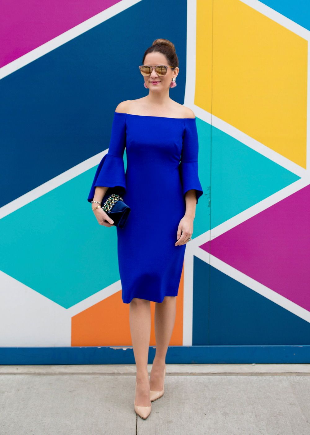 a1dff9e039aa Jennifer Lake Style Charade in a cobalt blue off shoulder bell sleeve dress,  velvet and crystal clutch, BaubleBar fringe earrings at a colorful Chicago  wall
