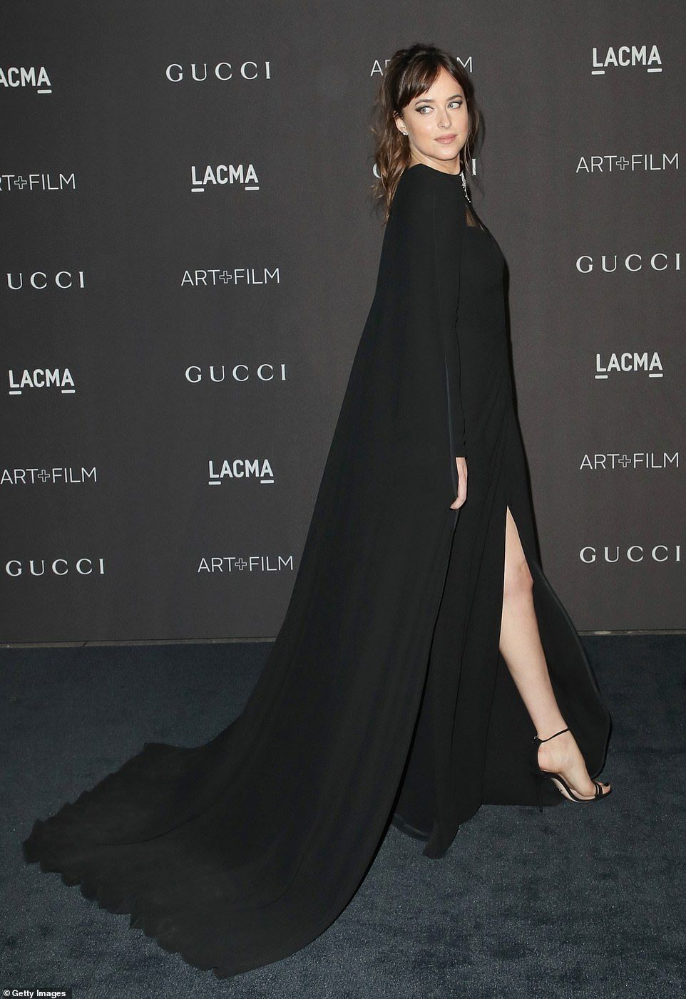 3c8c4e908 Showing some leg: The black dress featured a long flowing cape that trailed  behind the act.