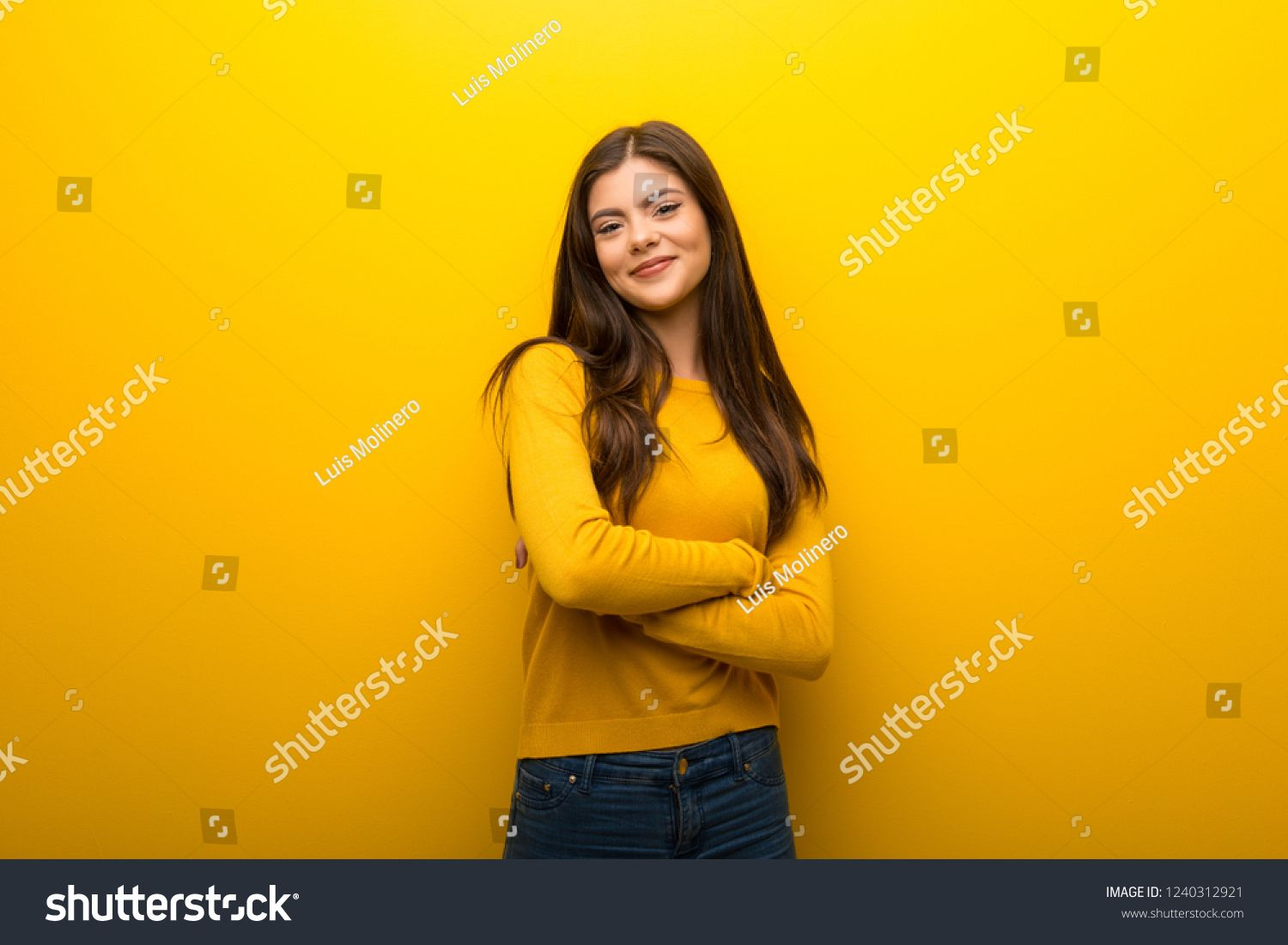Teenager Girl On Vibrant Yellow Background Keeping The Arms
