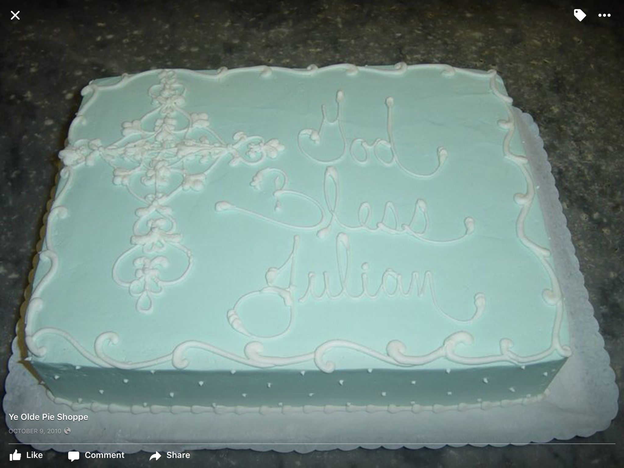 A Celtic cross piped with white buttercream frosting on a soft