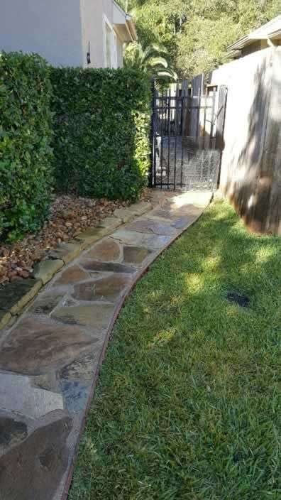 Flagstone walkway with polymer grout and polyboard edging.