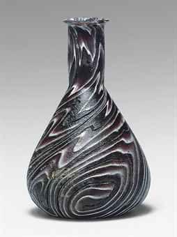 A ROMAN RIBBON GLASS BOTTLE  CIRCA 1ST CENTURY A.D.