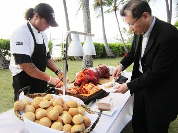 Whole roast pig lechon carving station served with rolls hoisin